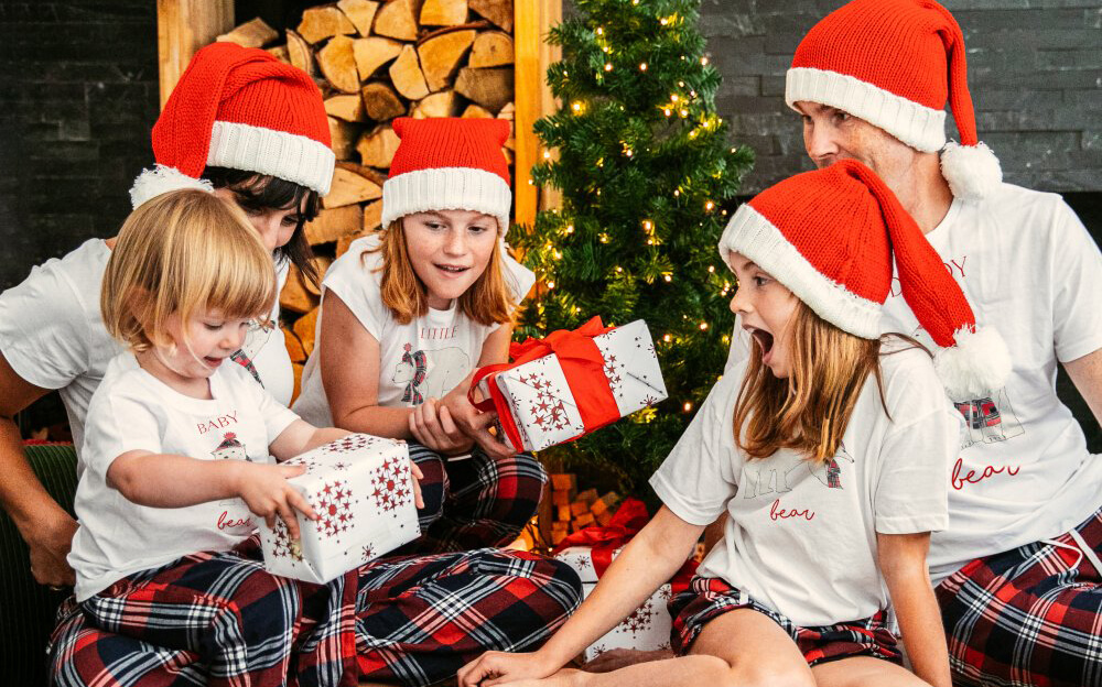 Family opening presents in front of the Christmas tree, wearing Bear Family Christmas Pyjamas